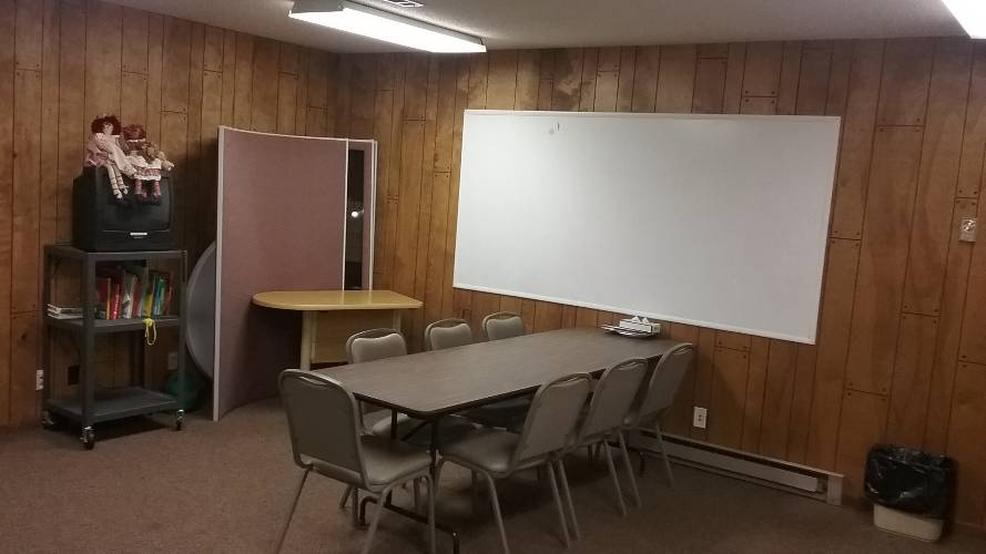 room with table, chairs, and white board